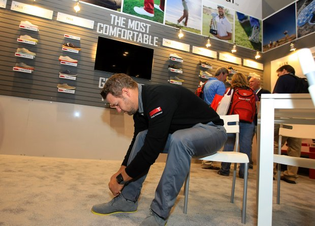 PGA Tour's Ryan Moore putting on the latest shoe at TRUE Linkswear booth at the 2014 PGA Merchandise Show at the Orange County Convention Center.