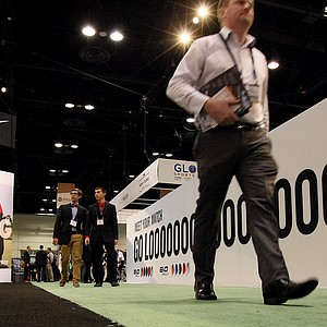 Patrons walk between Nike and Cobra Puma booths at the 2014 PGA Merchandise Show at the Orange County Convention Center.