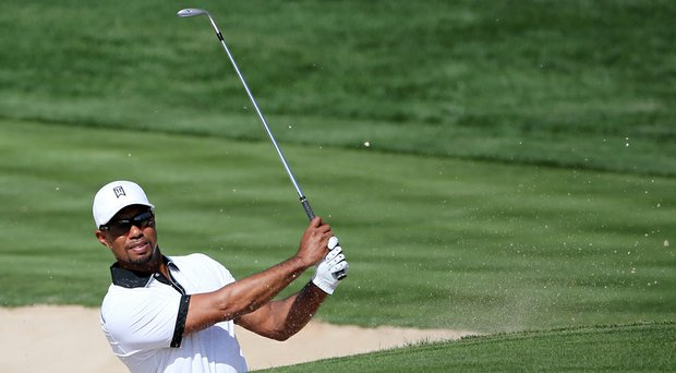 Tiger Woods plays a bunker shot on the third hole during a practice round for the Omega Dubai Desert Classic.