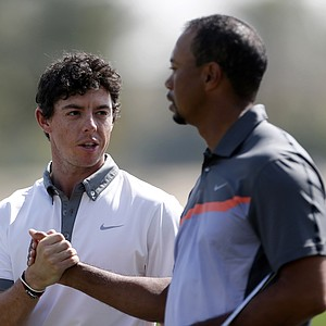 Rory McIlroy and Tiger Woods shake hands on the ninth green at the conclusion of the first round at the Omega Dubai Desert Classic.