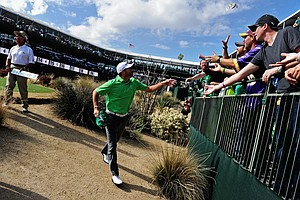 Michael Thompson throws money to spectators on the 16th hole during the third round of the Waste Management Phoenix Open.