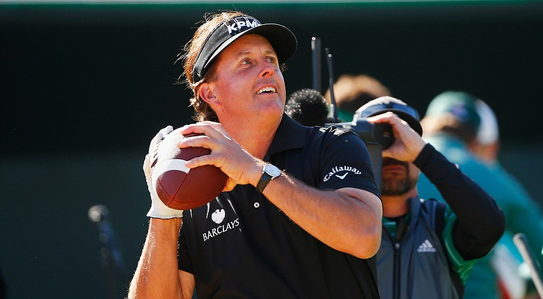 Phil Mickelson throws a football to the crowd on the 16th hole during the third round of the Waste Management Phoenix Open at TPC Scottsdale.