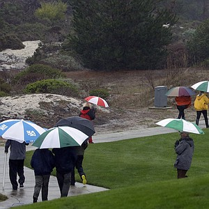 The gallery trudges along the course during a wet first round of the PGA Tour's 2014 AT&T Pebble Beach National Pro-Am.