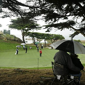 Fans try to avoid the rain while watching Stuart Appleby and Mike Weir during a wet first round of the PGA Tour's 2014 AT&T Pebble Beach National Pro-Am.