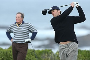 Quarterback Tom Brady of the NFL's New England Patriots hits as his head coach, Bill Belichick, looks on during the second round of the AT&T Pebble Beach National Pro-Am.