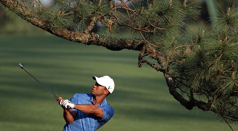 """Tiger Woods hits from beneath the """"Eisenhower Tree"""" during the 2011 Masters at Augusta National. Woods injured his achilles tendon hitting the shot."""