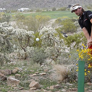 Victor Dubuisson hits a recovery shot from up against a shrub and goes on to save par on the second playoff hole of the 2014 WGC-Accenture Match Play before losing to Jason Day.