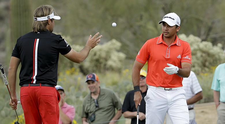 Victor Dubuisson tosses Jason Day's ball to him during their final at the 2014 WGC-Accenture Match Play at Dove Mountain in Marana, Ariz.