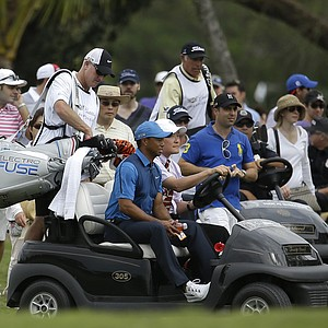Tiger Woods gets a ride in a cart after play was suspended during the first round of the WGC-Cadillac Championship at Trump National Doral.
