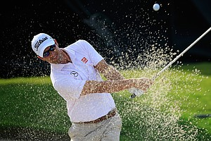 Adam Scott hits a bunker shot on the 11th hole during the weather-delayed first round of the WGC-Cadillac Championship at Trump National Doral.