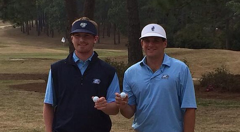 Seniors Hayden Anderson and Will Evans pose with their hole-in-one balls at the Schenkel Invitational.