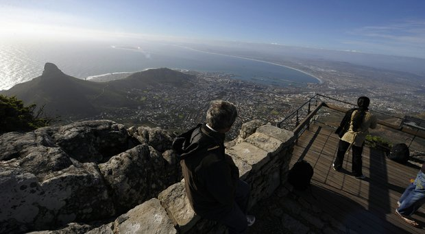 Tourists take pictures of the city of Cape Town as seen from the top of Table Mountain at the arrival station of the Table Mountain cableway. Table Mountain cableway has been running for over 80 years and the cars feature a floor which can rotate while ascending to give passengers a 360-degree panoramic views.