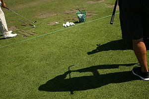 Club cleaning action on the practice range during Round 2 of the Arnold Palmer Invitational at Bay Hill Lodge and Club.