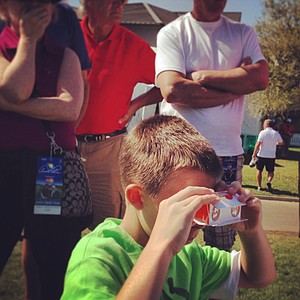 Bryce Lorenz, 14, of Apopka uses some disposable binoculars from MasterCard during Round 2 of the Arnold Palmer Invitational at Bay Hill Lodge and Club.
