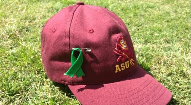 Arizona State players pinned a green ribbon to their hats in honor of Ron Balicki, who is battling cancer.