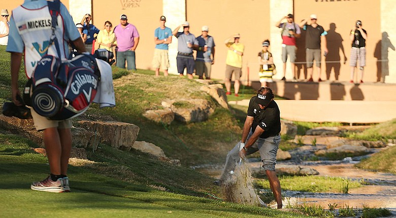 Phil Mickelson hits a shot from the edge of a water hazard at the par-5 18th during the second round of the Valero Texas Open. Mickelson birdied the hole.