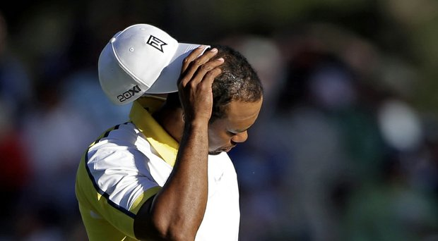 For the first time in 20 years, the Masters won't see Tiger Woods at Augusta National in 2014 (shown here reacting to his ball hitting the pin and going in the water last year).