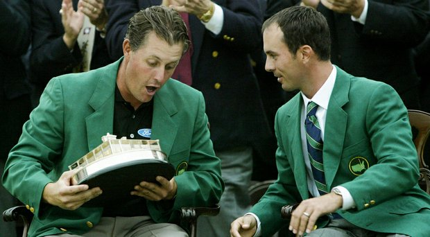 Phil Mickelson holds the Masters trophy after his 2004 win at Augusta National while talking to 2003 winner Mike Weir.