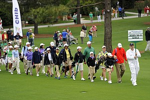 Competitors in the girls' 10-11 category, walk to the drive contest during the National Finals of the 2014 Drive, Chip and Putt Championships at Augusta National.