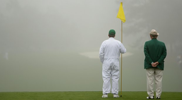 A caddie holds a flag pin during a practice round prior to the start of the 2014 Masters.