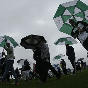 Patrons check out some Masters prep before rough weather forced an early end to practice Monday at Augusta National.
