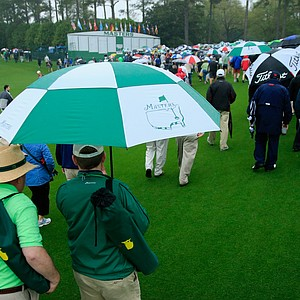 Masters patrons make use of their umbrellas amid rough weather that forced an early end to practice Monday at Augusta National.