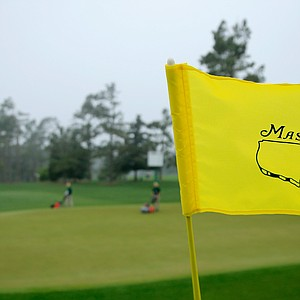 A Masters flagstick, like the trees in the background, bend in the wind amid rough weather that forced an early end to practice Monday at Augusta National.
