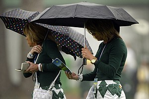 Patrons watch some Masters prep before rough weather forced an early end to practice Monday at Augusta National.