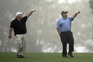 Craig Stadler, left, and Kevin Stadler get in some Masters prep before rough weather forced an early end to practice Monday at Augusta National.