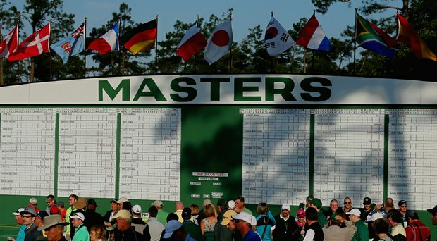 Patrons walk in front of a leaderboard near the first fairway during a practice round prior to the start of the 2014 Masters.