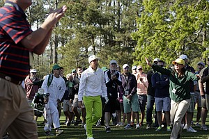 Rickie Fowler walks out of the rough as a volunteer tries to stop a patron during Thursday's first round of the 2014 Masters at Augusta National.