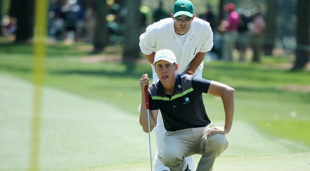 Oliver Goss lines up a putt on the first green with the help of caddie Brian Tam at the 2014 Masters.