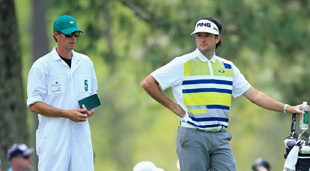 Bubba Watson leans on his bag while caddie Ted Scott checks a yardage during Friday's second round of the 2014 Masters at Augusta National.