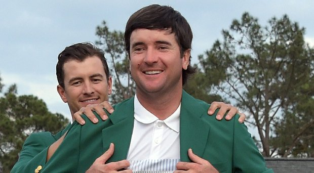 Bubba Watson, after winning the Masters for the second time, receives the green jacket of Augusta National from last year's champion, Adam Scott.