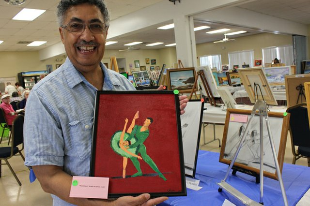 Emerging artist Victor Pagan poses with his first foray into painting on canvas, a portrait of ballerinas mid-dance.
