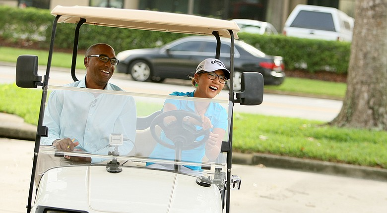 Lydia Ko with Damon Hack as they do a mock driving test in a golf cart at Golf Channel studios in Orlando.