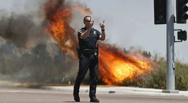 A Carlsbad, Calif., police officer turns traffic away from a wildfire Thursday.