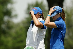 Florida's head coach Emily Glaser and Camilla Hedberg hold onto their hats during the first round the Women's 2014 Golf Championships at Tulsa Country Club