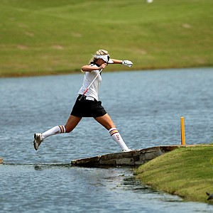 USC's Sophia Popov jumps over the water to take a drop after chipping her second shot into the water at No. 14 during the first round the Women's 2014 Golf Championships at Tulsa Country Club.