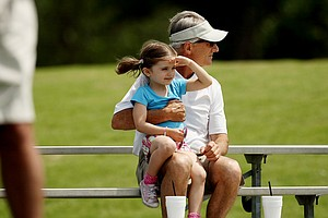 Tulsa Country Club member, Chris Bourne, and his granddaughter, Campbell James, 5, watch the morning golf during the second round of the 2014 NCAA Women's Golf Championships at Tulsa Country Club.