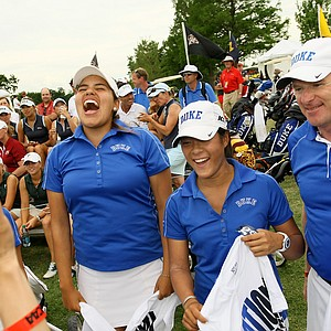 Duke's Alejandra Congrejo and Celine Boutier, center, celebrate alongside with head coach, Dan Brooks, during the final round of the Women's 2014 NCAA Division 1 Golf Championships at Tulsa Country Club.