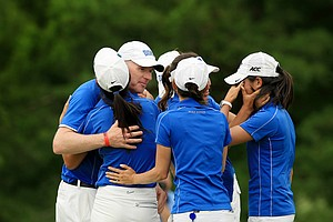 Duke head coach, Dan Brooks, hugs his team as Celine Boutier is overcome with emotion, far right, after they won the Women's 2014 NCAA Division 1 Golf Championships at Tulsa Country Club.
