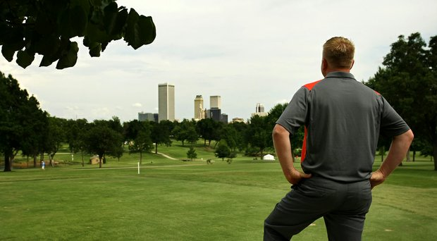 Golfweek's Lance Ringler looks out over the course with a view of the Tulsa skyline during the final round of the Women's 2014 NCAA Division 1 Golf Championships at Tulsa Country Club.