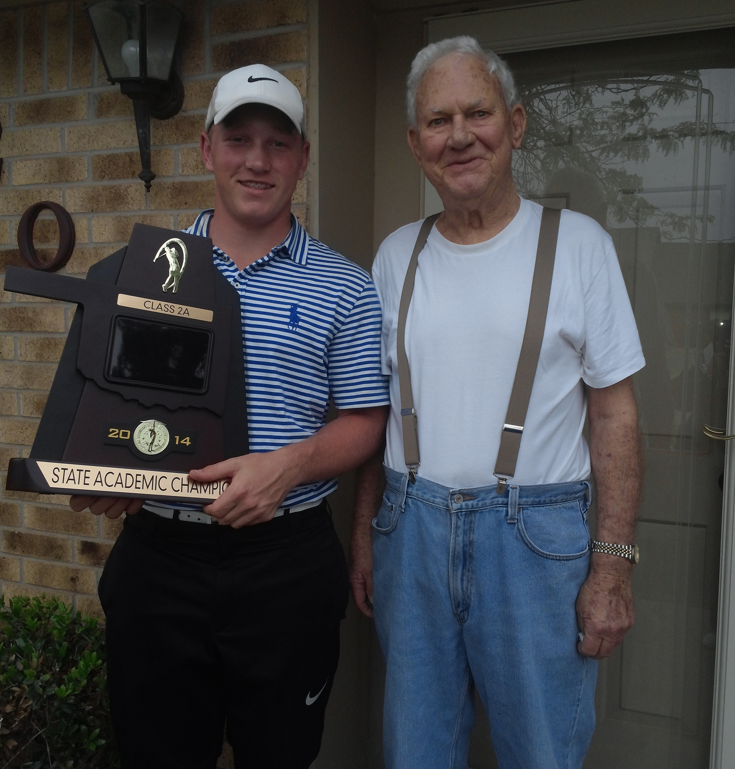 Brad Dalke holds the Oklahoma 2A Academic State Championship trophy alongside one of his biggest supporters in Hobart, Okla., Byron Shook.