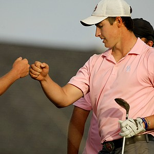 Oklahoma's Charlie Saxon fist bumps with a teammate as he leaves the 8th tee on Saturday during the NCAA Men's Division 1 Championship at Prairie Dunes Country Club in Hutchinson, Kan.