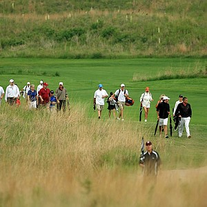 Players, parents, coaches and spectators head back to the clubhouse after the horn was sounded at 10:02 a.m. on Sunday of the NCAA Men's Division 1 Championship at Prairie Dunes Country Club in Hutchinson, Kan.