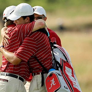 Alabama head coach, Jay Seawell, hugs senior Cory Whitsett after they defeated LSU during Tuesday semifinals of match play of the NCAA Men's Division 1 Championship at Prairie Dunes Country Club in Hutchinson, Kan.