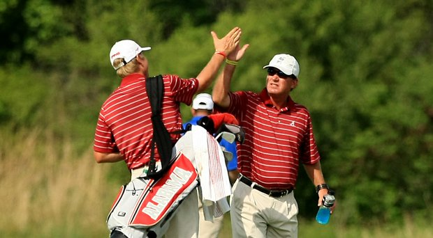 Alabama head coach Jay Seawell high-fives senior Trey Mullinax upon learning they defeated LSU during Tuesday's semifinals at the NCAA Division I Men's Championship at Prairie Dunes Country Club in Hutchinson, Kan.