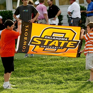 Noah Bratton, 11,  and Gunnar Bratton, 10, children of Oklahoma State coach, Alan Bratton, unfurl a flag after they defeated Stanford in Tuesday's semifinals of match play of the NCAA Men's Division 1 Championship at Prairie Dunes Country Club in Hutchinson, Kan.