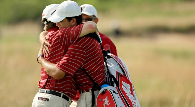 Alabama head coach Jay Seawell, hugs senior Cory Whitsett after the Crimson Tide advanced during match play Tuesday the NCAA Division I Men's Championship at Prairie Dunes Country Club in Hutchinson, Kan.